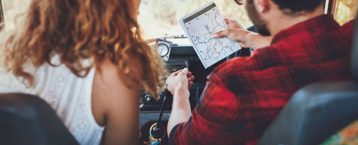 a man and woman in a car looking at a map