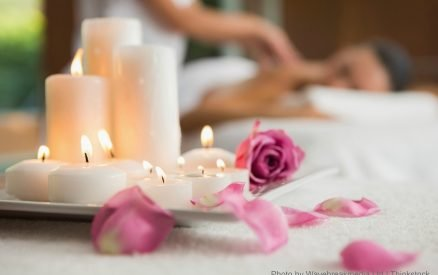 Candles and rose petals on massage table at the health spa